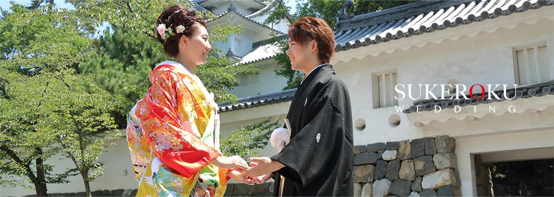 結婚式の前撮り。岐阜県大垣市にある大垣城をバックに、手をつなぐ新郎新婦。